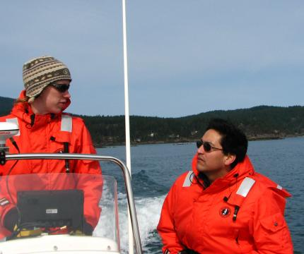Alejandro and a student talking while on a boat