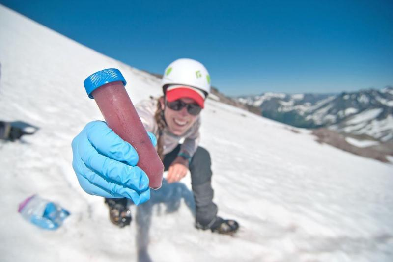 student holding tube of watermelon snow while crouching on a snowy mountain