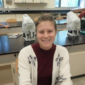 Amanda Stromecki sits at a lab table and smiles, microscopes in background