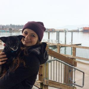 Micaela Pribic holds a small dog on the Boulevard boardwalk, Bellingham Bay in background