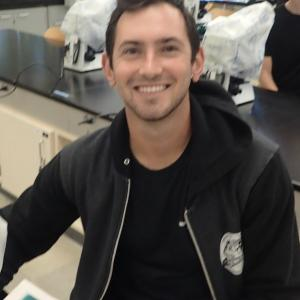 Jake Lawlor smiles while sitting at lab table, focus blurred