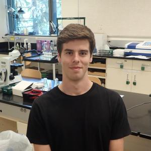 Weston Staubus sits at a lab table next to a microscope, various lab equipment in background